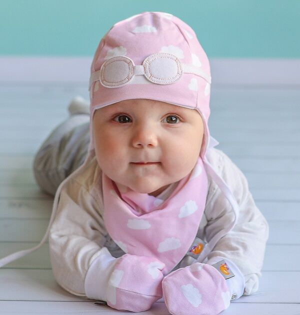 newborn baby wearing matching gift set - pink and white cloud hat, bib and gloves