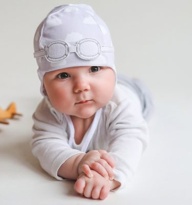 newborn wearing grey pilot hat