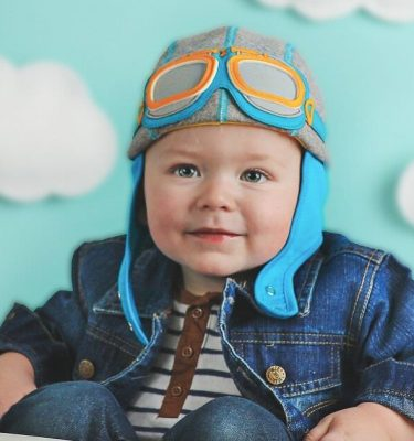 boy wearing grey and blue baby pilot hat