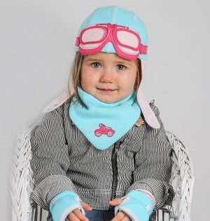 girl wearing matching blue and pink baby gift set. Hat, bib and gloves.