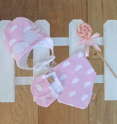 newborn baby wearing matching gift set - pink hat bib and gloves