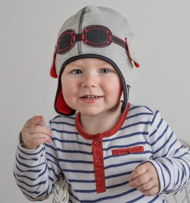 boy wearing grey pilot baby hat