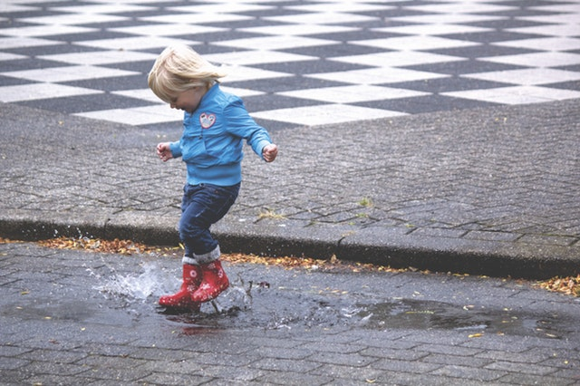 young boy jumping puddle